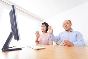パソコンでテレビ電話をする高齢の夫婦の写真素材 [FYI04713008]
