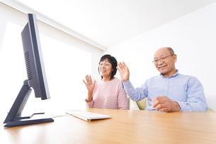 パソコンでテレビ電話をする高齢の夫婦の写真素材 [FYI04713009]