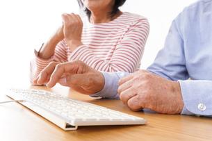 パソコンを使う高齢の夫婦の写真素材 [FYI04713012]