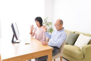 パソコンでテレビ電話をする高齢の夫婦の写真素材 [FYI04713013]