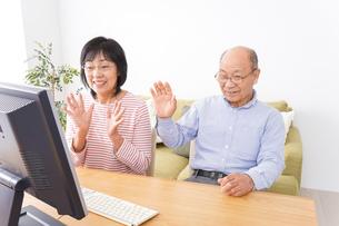 パソコンでテレビ電話をする高齢の夫婦の写真素材 [FYI04713026]