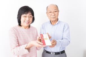 お祝いを渡すシニアの夫婦の写真素材 [FYI04713041]