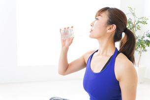 水分を摂取するスポーツウェアの女性の写真素材 [FYI04713235]