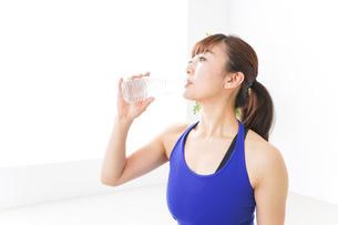 水分を摂取するスポーツウェアの女性の写真素材 [FYI04713236]