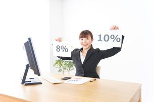 消費税増税の対応をする若いビジネスウーマンの写真素材 [FYI04713362]