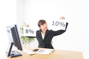 消費税増税の対応をする若いビジネスウーマンの写真素材 [FYI04713363]