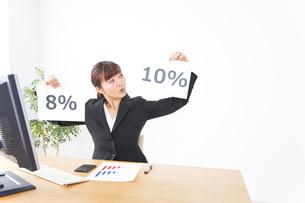 消費税増税の対応をする若いビジネスウーマンの写真素材 [FYI04713364]