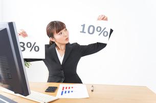 消費税増税の対応をする若いビジネスウーマンの写真素材 [FYI04713368]