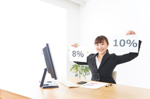 消費税増税の対応をする若いビジネスウーマンの写真素材 [FYI04713369]