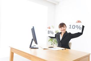 消費税増税の対応をする若いビジネスウーマンの写真素材 [FYI04713370]