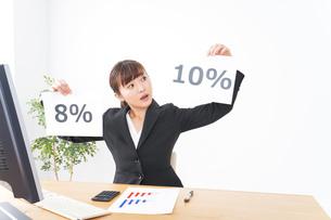 消費税増税の対応をする若いビジネスウーマンの写真素材 [FYI04713371]