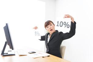 消費税増税の対応をする若いビジネスウーマンの写真素材 [FYI04713372]