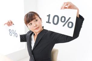 消費税増税の対応をする若いビジネスウーマンの写真素材 [FYI04713373]