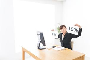 消費税増税の対応をする若いビジネスウーマンの写真素材 [FYI04713377]