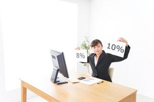 消費税増税の対応をする若いビジネスウーマンの写真素材 [FYI04713379]