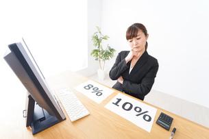 消費税増税の対応をする若いビジネスウーマンの写真素材 [FYI04713381]