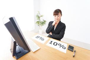 消費税増税の対応をする若いビジネスウーマンの写真素材 [FYI04713382]