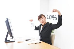 消費税増税の対応をする若いビジネスウーマンの写真素材 [FYI04713383]