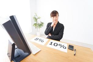 消費税増税の対応をする若いビジネスウーマンの写真素材 [FYI04713387]