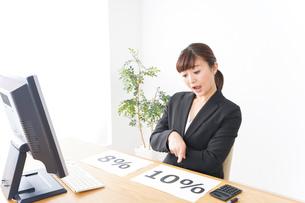 消費税増税の対応をする若いビジネスウーマンの写真素材 [FYI04713389]