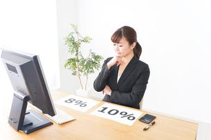 消費税増税の対応をする若いビジネスウーマンの写真素材 [FYI04713391]