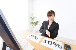 消費税増税の対応をする若いビジネスウーマンの写真素材 [FYI04713394]