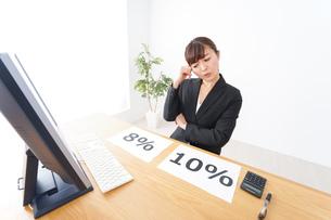消費税増税の対応をする若いビジネスウーマンの写真素材 [FYI04713396]
