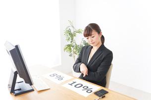 消費税増税の対応をする若いビジネスウーマンの写真素材 [FYI04713397]