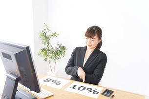 消費税増税の対応をする若いビジネスウーマンの写真素材 [FYI04713399]