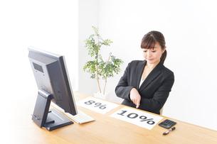 消費税増税の対応をする若いビジネスウーマンの写真素材 [FYI04713400]