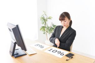 消費税増税の対応をする若いビジネスウーマンの写真素材 [FYI04713404]