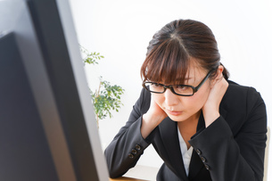 過労・長時間労働・残業に苦しむビジネスウーマンの写真素材 [FYI04713423]