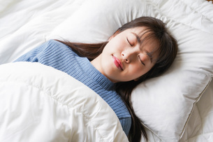 布団に入って睡眠を取る若い女性の写真素材 [FYI04713567]