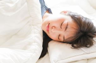 布団に入って睡眠を取る若い女性の写真素材 [FYI04713569]