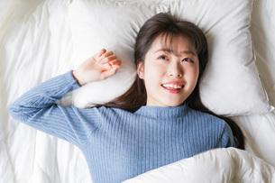 布団に入って睡眠を取る若い女性の写真素材 [FYI04713571]