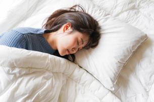 布団に入って睡眠を取る若い女性の写真素材 [FYI04713574]