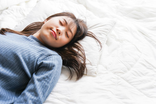 布団に入って睡眠を取る若い女性の写真素材 [FYI04713577]