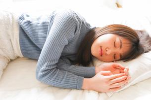 布団に入って睡眠を取る若い女性の写真素材 [FYI04713584]