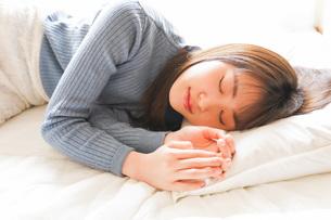 布団に入って睡眠を取る若い女性の写真素材 [FYI04713585]