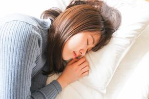 布団に入って睡眠を取る若い女性の写真素材 [FYI04713588]