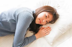 布団に入って睡眠を取る若い女性の写真素材 [FYI04713589]