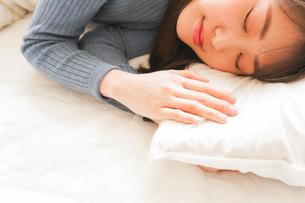 布団に入って睡眠を取る若い女性の写真素材 [FYI04713590]