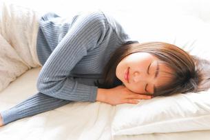 布団に入って睡眠を取る若い女性の写真素材 [FYI04713591]