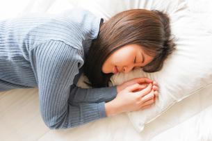 布団に入って睡眠を取る若い女性の写真素材 [FYI04713593]