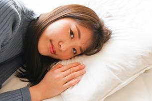 布団に入って睡眠を取る若い女性の写真素材 [FYI04713594]