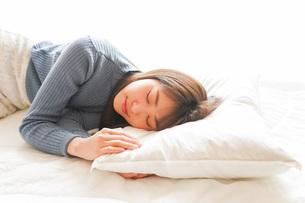 布団に入って睡眠を取る若い女性の写真素材 [FYI04713596]