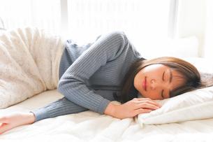 布団に入って睡眠を取る若い女性の写真素材 [FYI04713598]
