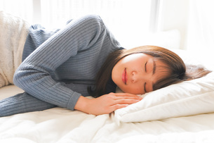 布団に入って睡眠を取る若い女性の写真素材 [FYI04713599]