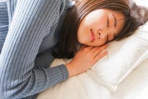 布団に入って睡眠を取る若い女性の写真素材 [FYI04713601]