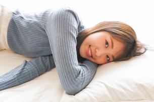 布団に入って睡眠を取る若い女性の写真素材 [FYI04713603]